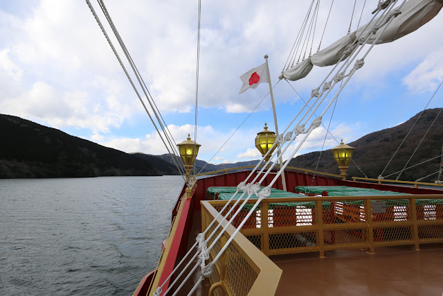 The rear view of Hakone Sightseeing Cruise ship with Japan flag along Lake Ashinoko in Japan