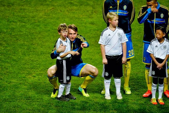 Sweden player Kim Källström is seen trying to comfort a mascot who gets scared and nervous