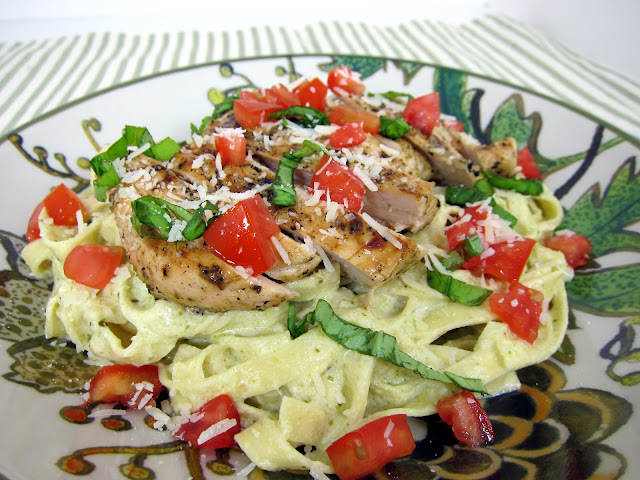 Chicken Pesto Alfredo Recipe - chicken marinated in Italian dressing and pesto then grilled. Served over a bed of fettuccine pesto Alfredo - SO delicious and ready in under 20 minutes!