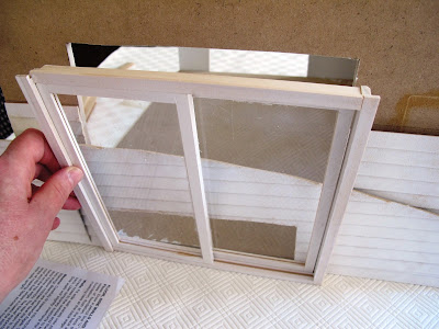 Half-built dolls' house shed with weatherboard cladding, some of which has fallen into the doorway.