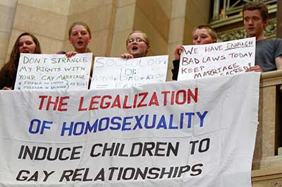 Neatly handmade banner hanging from a Capitol railing reads THE LEGALIZATION OF HOMOSEXUALITY INDUCE CHILDREN TO GAY RELATIONSHIPS
