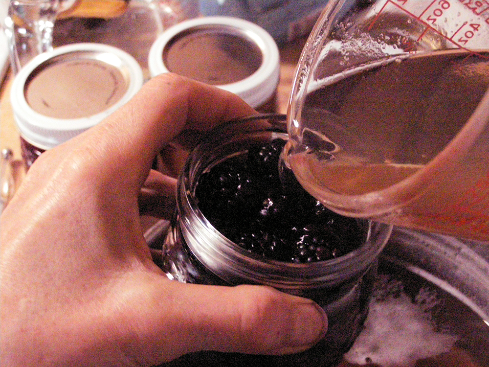 Hands Pouring Hot Syrup into Jar of Blackberries with Measuring Cup