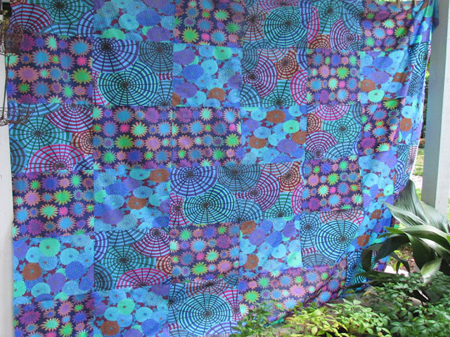 "Three Kaffe Fassett fabrics cut into 12"" squares, arranged into pleasing combination, then resewn."
