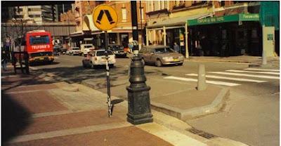 Vista de acerado y calzada con paso de peatones señalizado verticalmente con panel circular de color amarillo con dibujo de piernas y pies andando