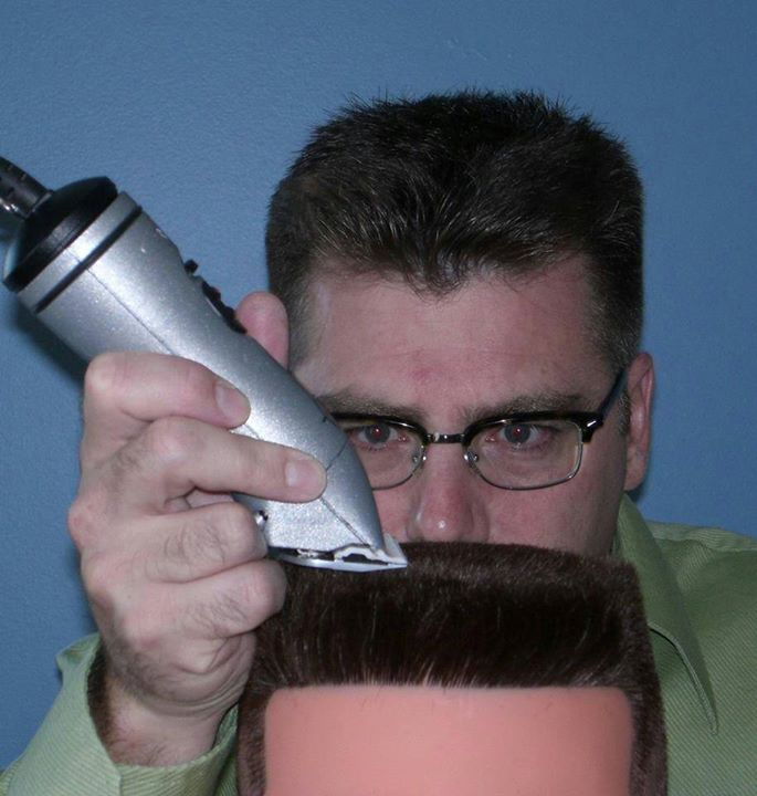 A barber training in a barbershop for a Flat Top haircut.