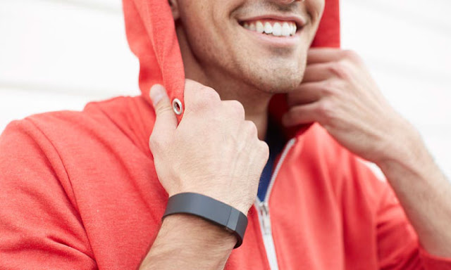 A man in a red hoodie shows off his black Fitbit, a popular activity tracker that measures steps, calories, distance traveled, etc.