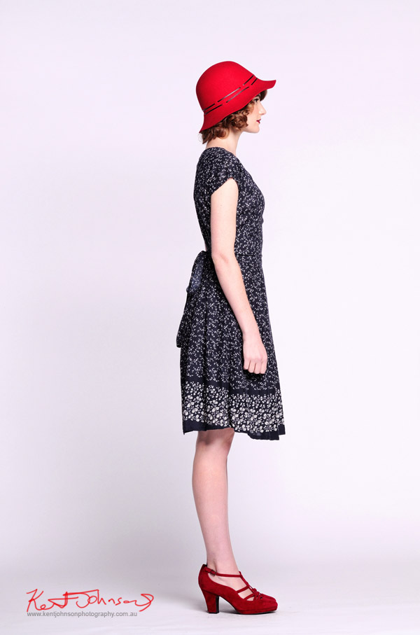 Blue print dress, soft felt hat in red, full length shot in profile - Vintage Fashion - Studio White Background -