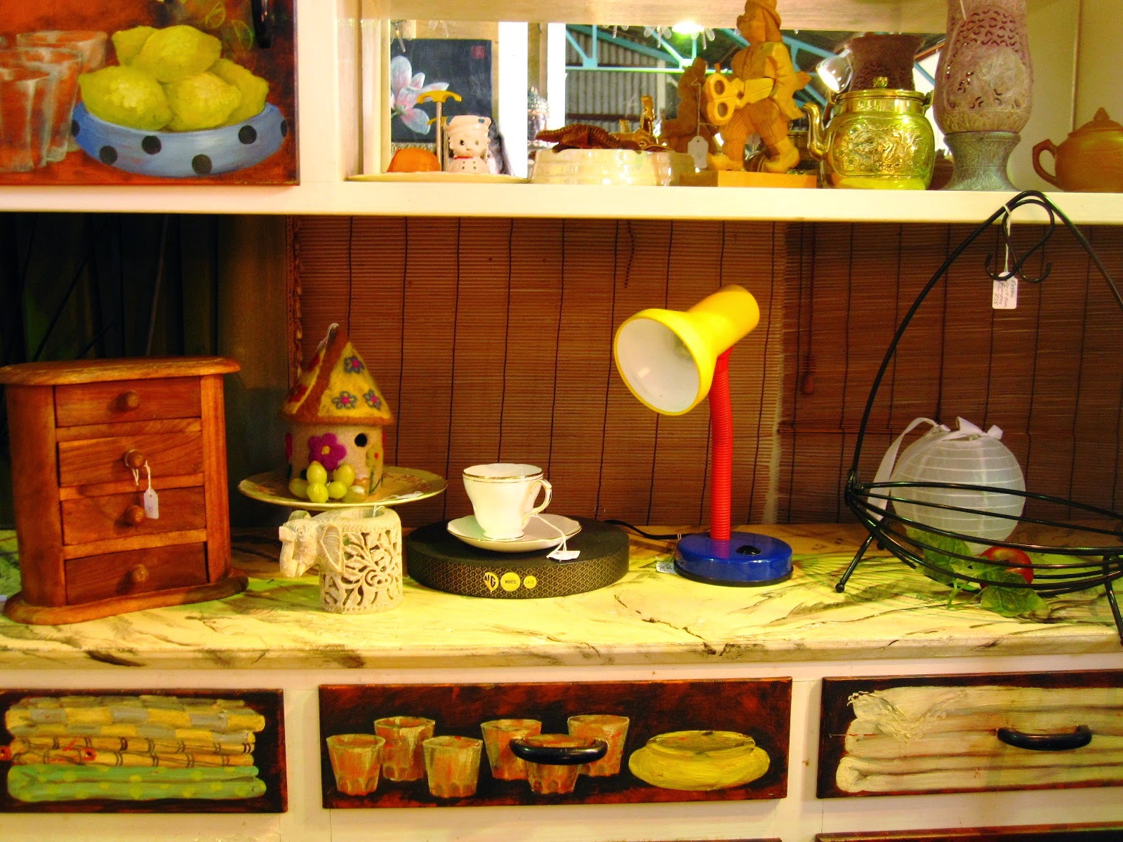 Vintage 1950s dresser, painted with trompe l'oeil of the contents of the cupboards and drawers. On it is displayed a number of items including a round house made of felt.