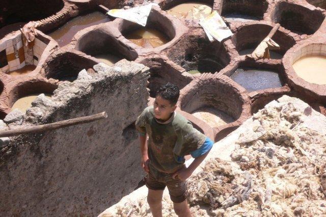 Joven trabajando en una curtiduría y tinajas repletas de tintes naturales en Fez, Marruecos