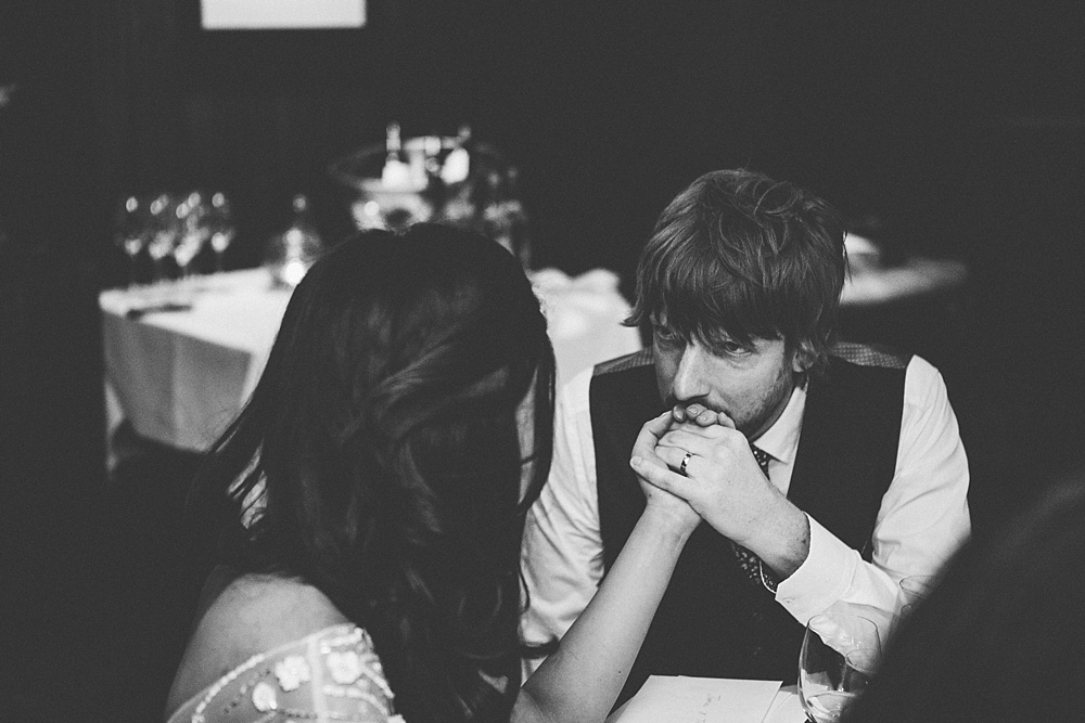 reportage photograph of groom kissing brides hand during wedding reception in black and white.