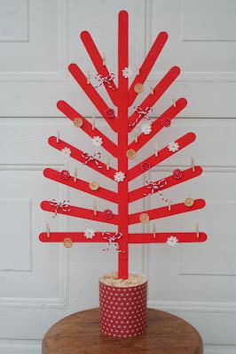 Árbol de navidad creado con palillos y decorado con lazos y botones.