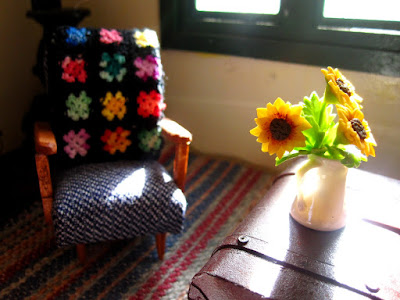 Modern dolls' house miniature armchair with afghan rug on the back, and chest with a vase of sunflowers on top.