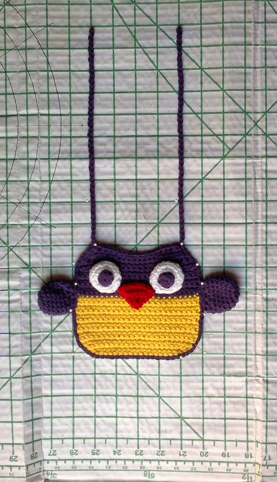 Crocheted owl bib laid out on blocking board grid.