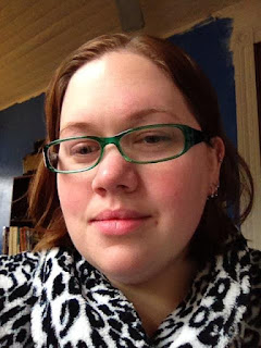 Author with wet auburn hair, rosy skin, green plastic glasses, no makeup, wearing a snow leopard print fuzzy bathrobe. Wall is medium blue in background with a bookshelf visible