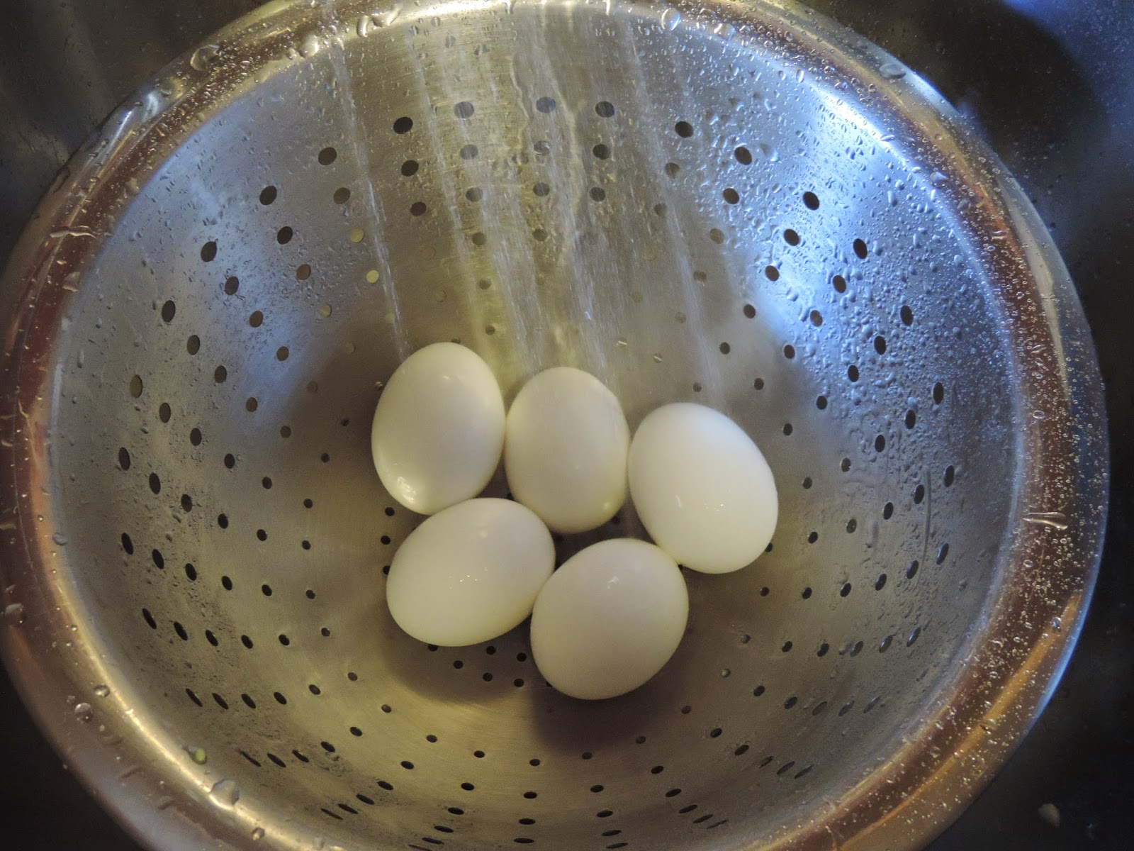 Cold water being poured over the hard boiled eggs.