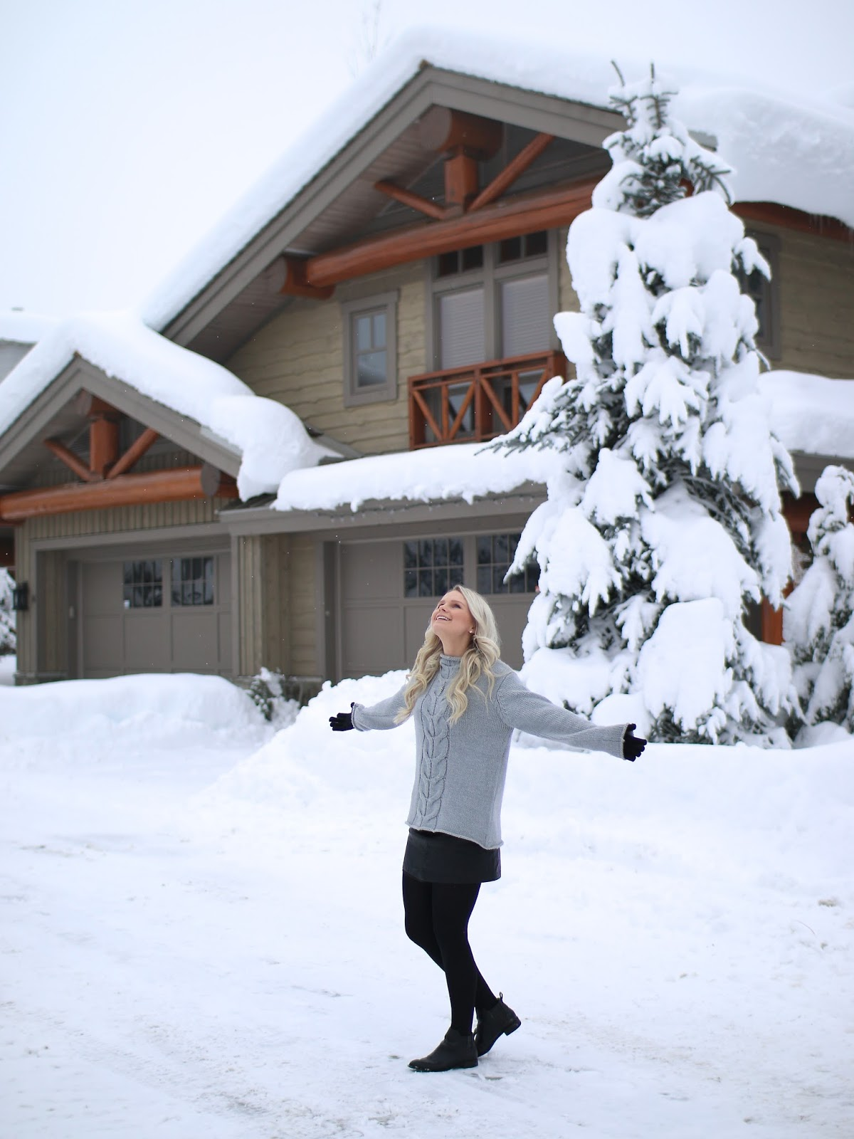 a women twirls in the falling snow in a beautiful cabin complex in whistler BC as the snow falls around her