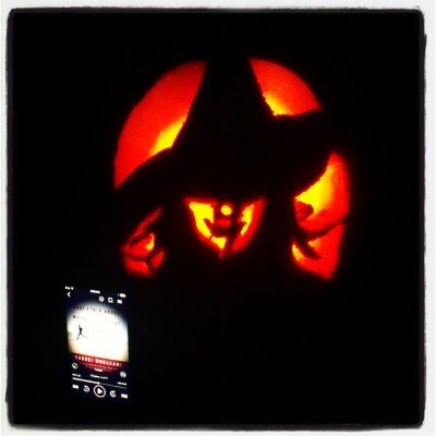 A pumpkin carved with Elphaba the Wicked Witch of the West's face appears in an otherwise dark space. Beside it is an iPod with the cover of What We Talk About When We Talk About Running on its screen. It features a person running across what appears to be a beach.