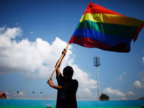 Membro de um grupo LGBT com uma bandeira arco íris no Nepal (Foto: AP Photo/Niranjan Shrestha)
