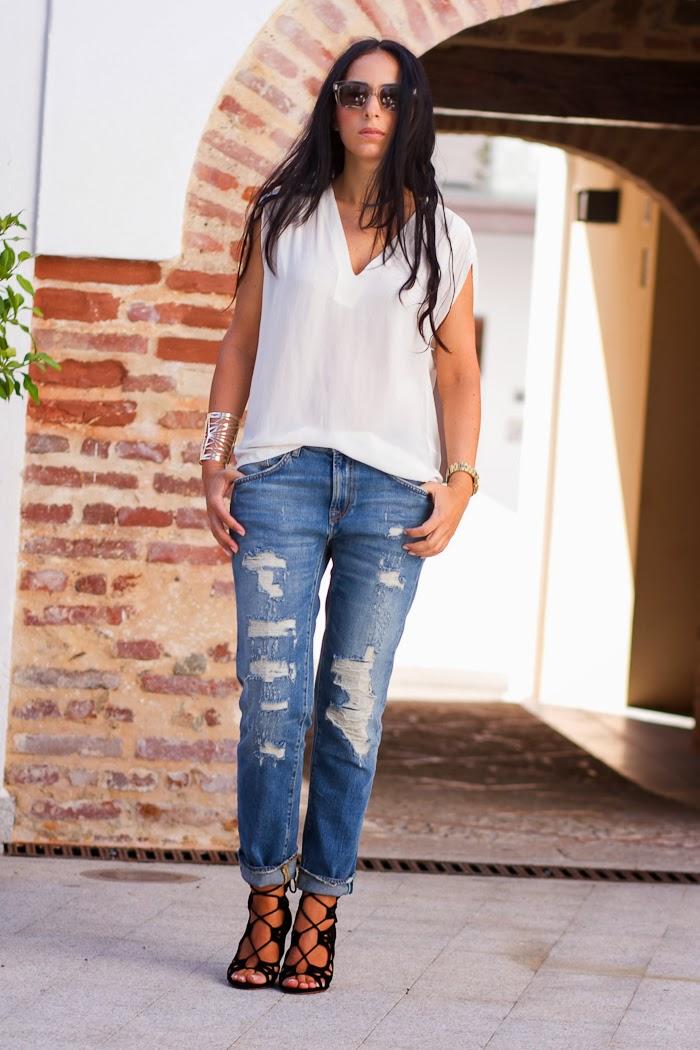 Blusa blanca, jeans rotos, brazalete dorado y sandalias acordonadas