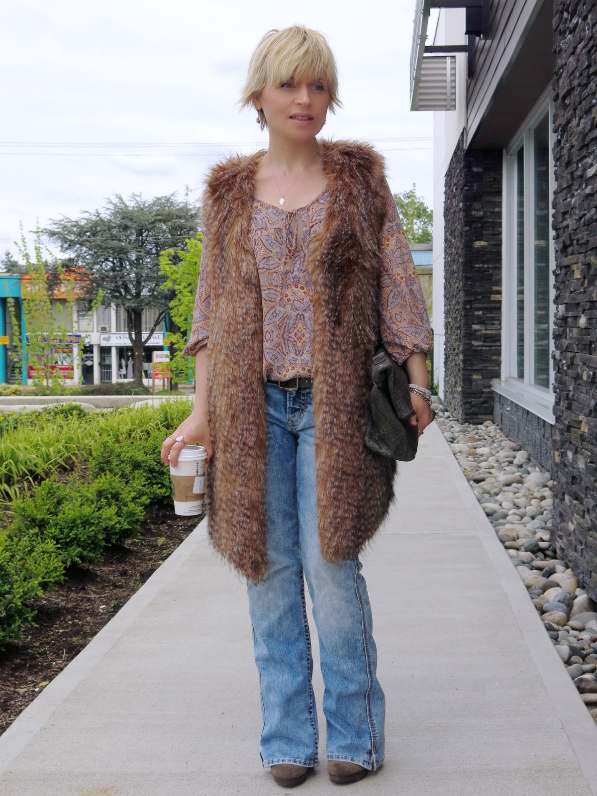 styling a paisley blouse with boot-cut jeans and a furry vest