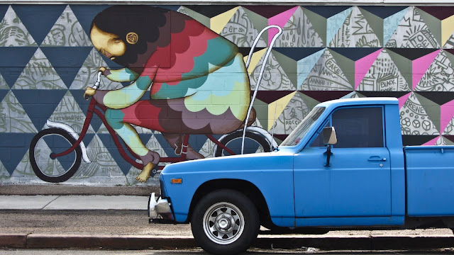 A really cool mural of a guy on a bike and a well kept, old blue pickup truck just north of downtown Denver.