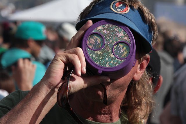 A pot smoker wearing a Grateful Dead visor and looking through a kaleidoscope at the Denver 420 smoke out.
