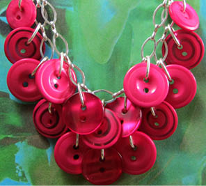 Necklace has layers of dark pink plunging buttons hanging from silver chain loops