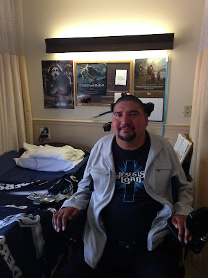 Juan Jose sits in an electric wheelchair in his room. You can see his bed and some posters up behind him.