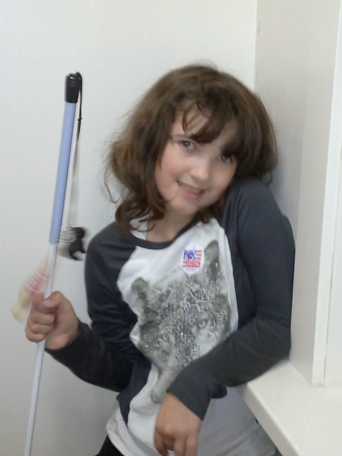 A girl with dark hair wearing a wolf long sleeve shirt and holding a white cane smiles