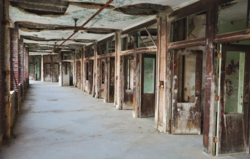 Inside the hallway of an abandoned mental institution … walls and ceiling are decayed and open to the air.