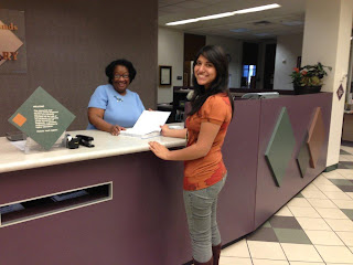 Image of Sandi Richey with student at circulation desk