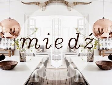 Miedziana lampa wisząca nad białym stołem w stylu skandynawskim
