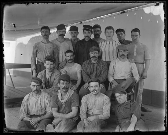 Black-and-white glass plate negative, 4 x 5 inches. Crew portrait of sixteen men seated and standing on an unidentified steamship's deck. All but 3 have mustaches.