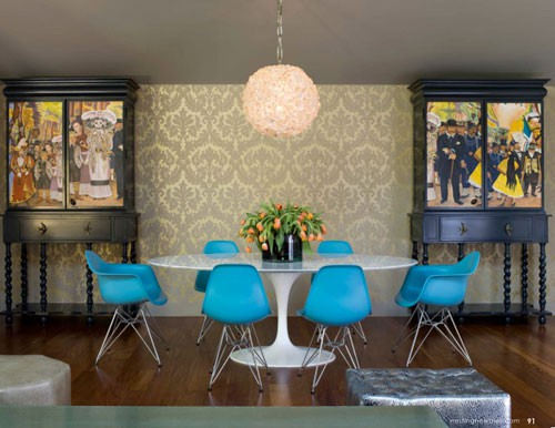 These Blue Eames Dining Chairs Around The Iconic Saarinen Tulip Table Look  Very Retro Against The 70s Fleur De Lis Style Wallpaper.