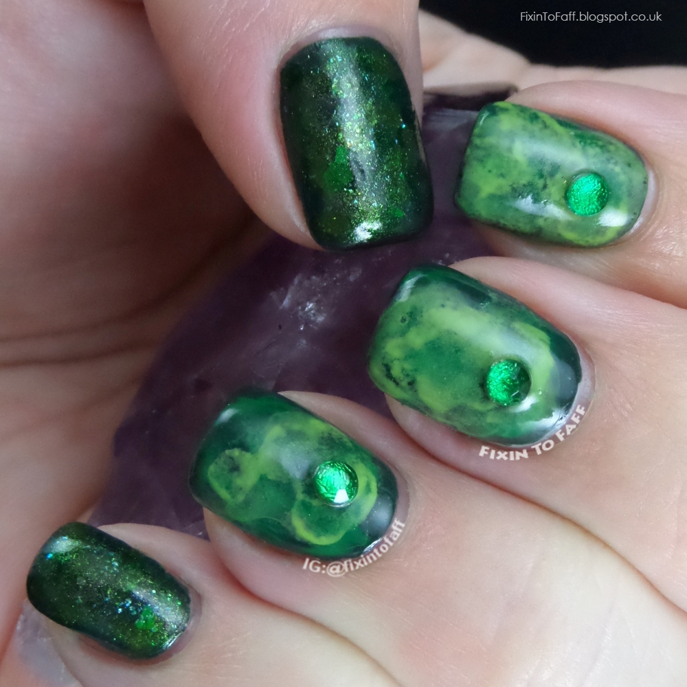 Green base sponged watercolor nail art with rhinestones and glitter accents.