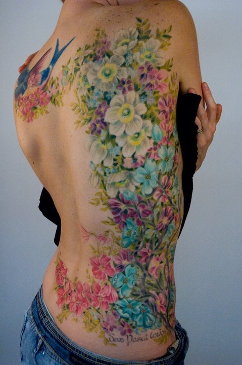Home » Back Tattoos » Colorful garden of flowers tattoo on back