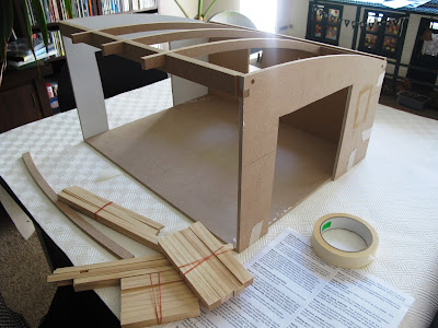 Half-built dolls' house shed sitting on a dining-room table.