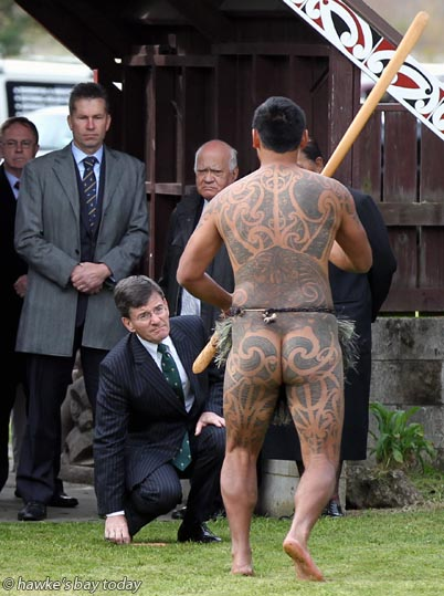 Centre: Chris Finlayson, Minister of Treaty Settlements, accepting the challenge of Rangitane Taurima, performs Te Wero, The Challenge - powhiri - Maungaharuru Tangitu Treaty Settlement Signing, Maungaharuru-Tangitu Trust, Tangoio Marae, Tangoio, Hawke's Bay photograph