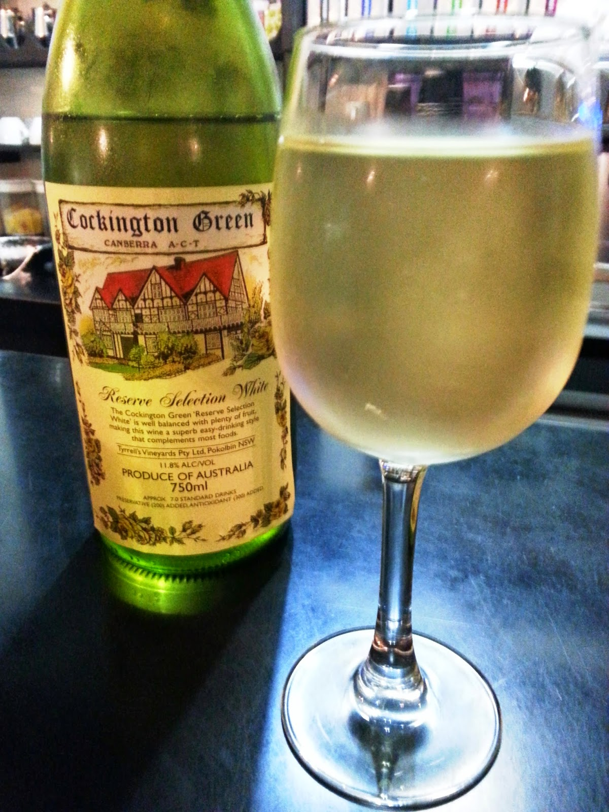 A bottle of special-label Cockington Green wine next to a glass of it.