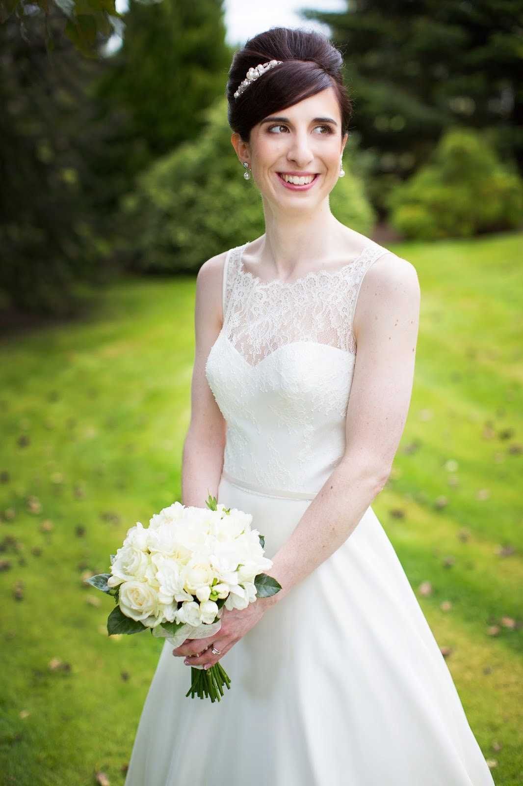 bride holding her bouquet smiling with her hair in a french roll accessorised with a jewelled band