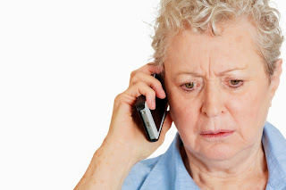 A concerned older woman listens on the phone.