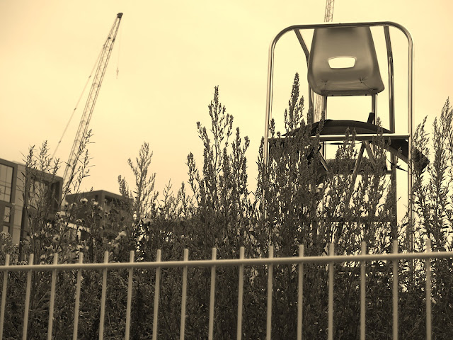 Sepia toned arty shot of the fence, cranes and lifeguard's chair at King's Cross Pong Club