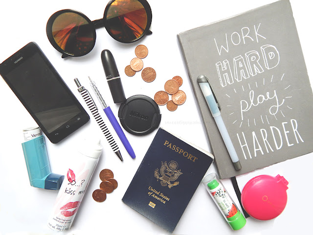 phone, inhaler, pens, spray, passport, mirror, notebook, sunglasses, lipstick, change, lip balm, phone on a white background