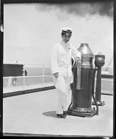 Black-and-white negative, 4 x 5 inches. Woman dressed in a ship captain's uniform wearing a fake mustache and goatee and leaning against the binnacle on the Manoa's (built 1913; merchant vessel) deck.