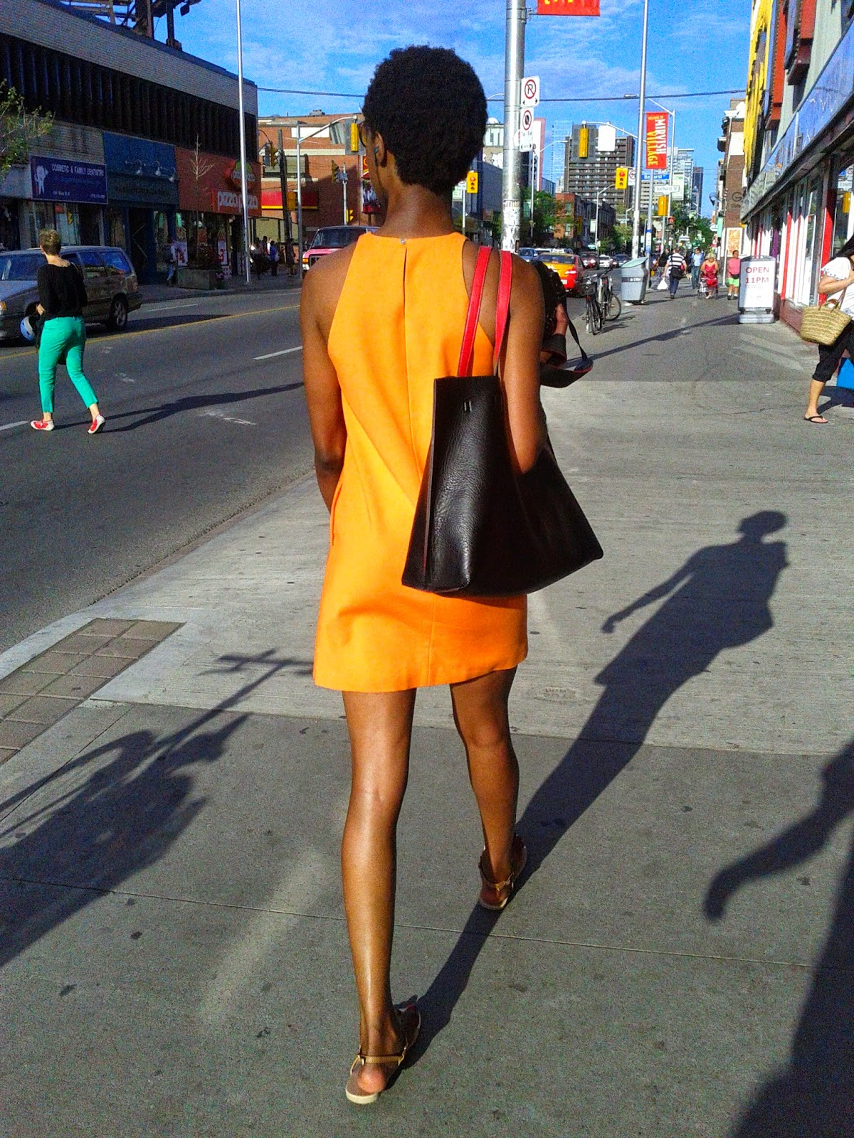 Stock photo: Black lady wearing an orange dress