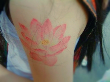 a light red lotus tattoo on the arm
