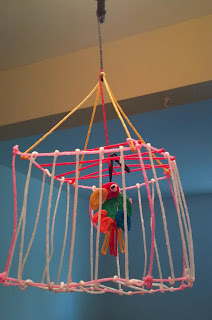 a parrot and a cage made of bendaroos