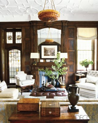 The built-in bookcase is original to the house; the Swedish alabaster  chandelier is circa 1895; the sofa, banquette, and ottoman were designed by  Gambrel.