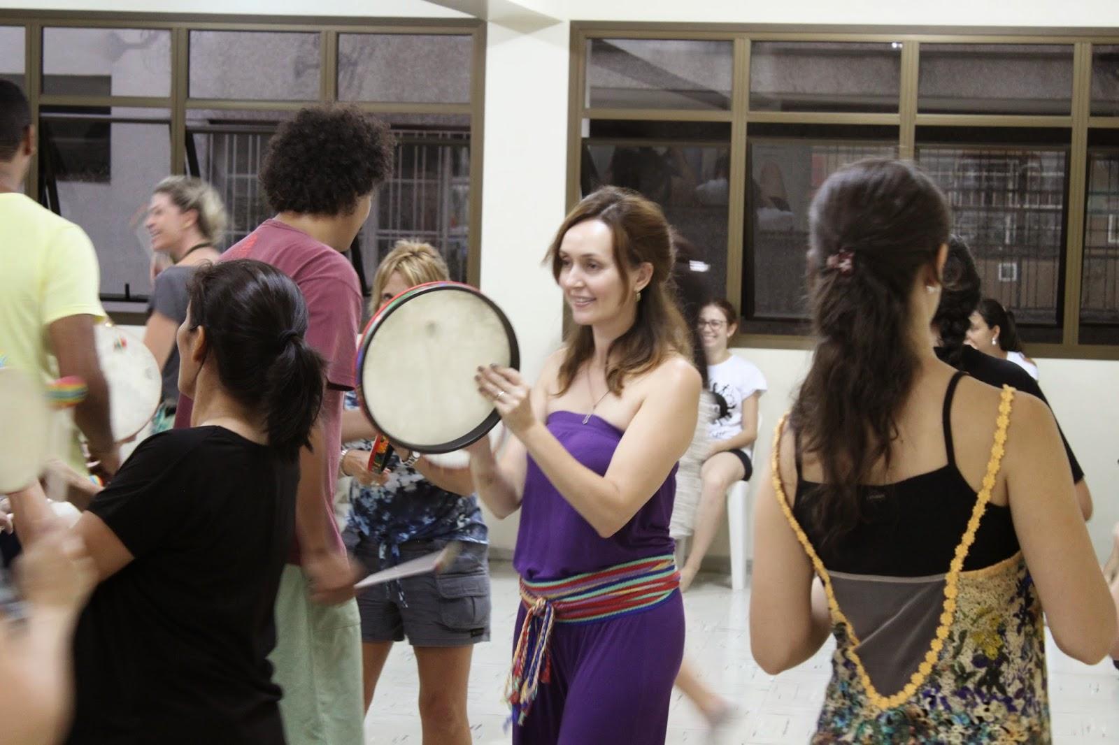 Descrição da Foto: Participantes estão caminhando tocando o tambor em diversas direções.