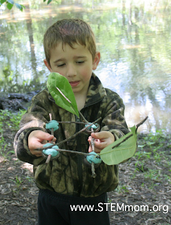 Kid holding small homemade boat made of nutshells, sticks, and leaves